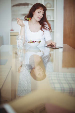 Pregnant woman using digital tablet while having salad at home LANG_EVOIMAGES