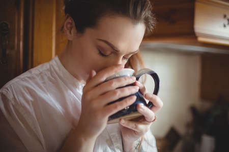 Woman having coffee in kitchen at home