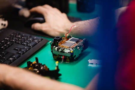 Close-up of a man working on desktop pc in an electronics repair centre LANG_EVOIMAGES