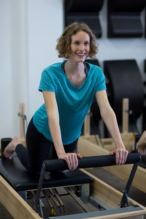 Smiling fit woman exercising on reformer in gym Stock Photo