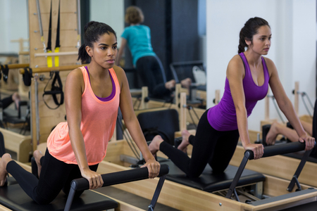 Fit women exercising on reformer in gym