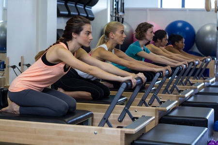 Determined women practicing stretching exercise on reformer in gym Stock Photo