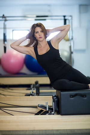 Portrait of woman practicing stretching exercise on reformer in gym