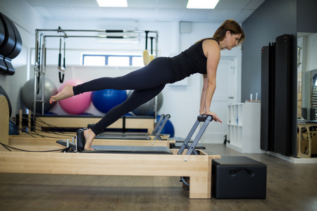 Determined woman practicing stretching exercise on reformer in gym