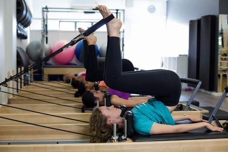 women s health: Group of women exercising on reformer in gym