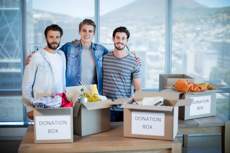 Portrait of smiling creative business team standing with donation box in office