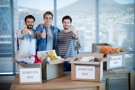 Creative business team standing near donation box and showing thumbs up in office