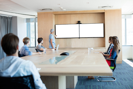 associate: Woman giving presentation to her colleagues in conference room at office Stock Photo