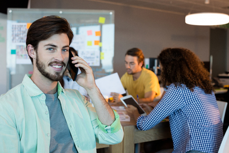 Smiling man talking on his mobile phone at office