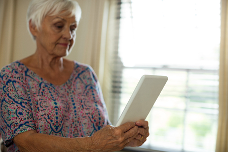 Senior woman holding digital tablet in living room at home