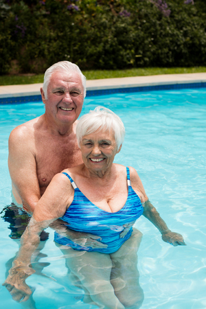 Portrait of happy senior couple in the pool on a sunny day