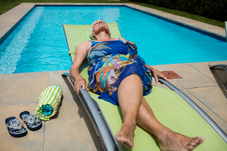 Senior woman sleeping on lounge chair at poolside Stock Photo