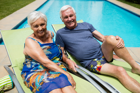 Portrait of senior couple relaxing on lounge chair at poolside Stock Photo