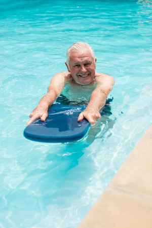 Senior man swimming in the pool on a sunny day