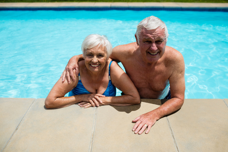 Portrait of happy senior couple relaxing together in pool