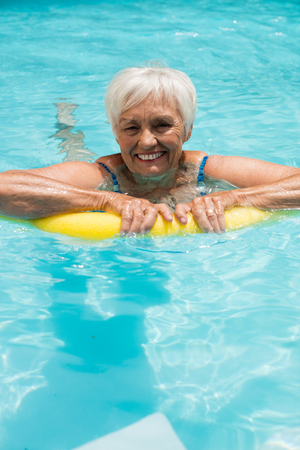 Senior woman swimming with inflatable tube in the pool