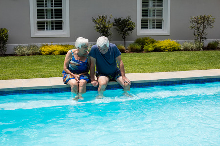 Happy senior couple interacting with each other at poolside