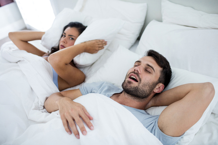 Woman getting disturbed with man snoring on bed in bedroom