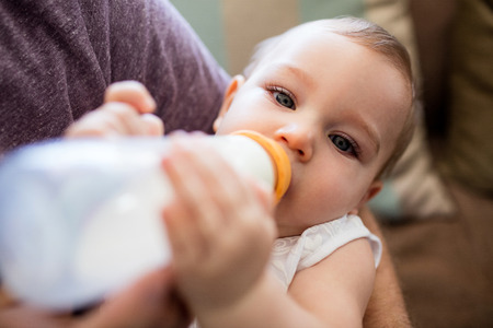 Father feeding milk to baby girl at home Stock Photo