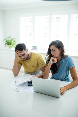 figuring: Worried couple calculating their bills with laptop in the kitchen at home