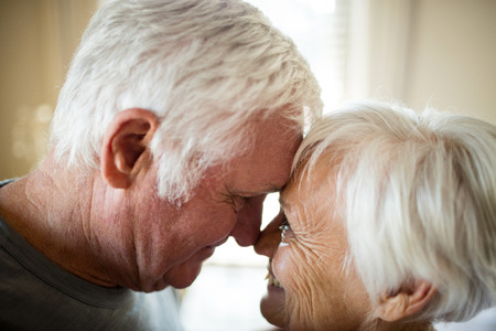 Senior couple romancing in bedroom at home Stock Photo