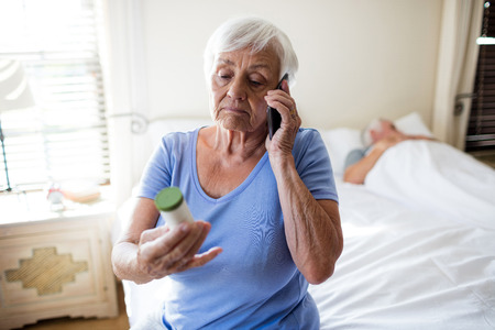 Woman talking on mobile phone and holding medicine prescription bottle in the bedroom at home