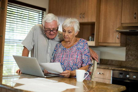 checking account: Senior couple calculating their invoices with laptop in the kitchen at home