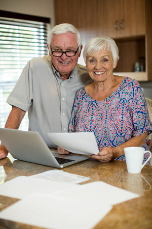 figuring: Senior couple calculating their invoices with laptop in the kitchen at home