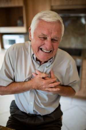 Senior man suffering from heart attack in the kitchen at home Stock Photo