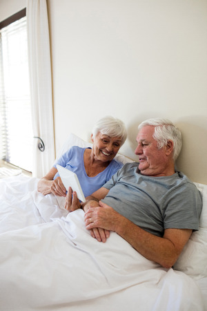Senior couple using digital tablet in the bedroom at home