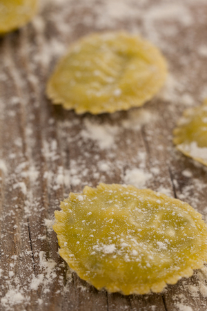 Close-up of round ravioli pasta dusted with floor on wooden background Stock Photo