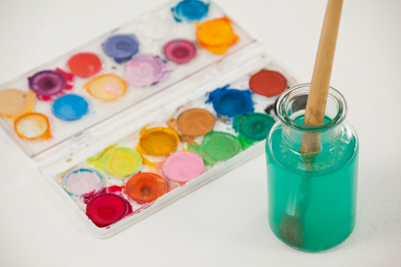 Watercolor palette and paint brush with blue paint dipped into water against white background