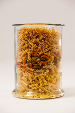 tight filled: Girandole pasta in a glass container against white background