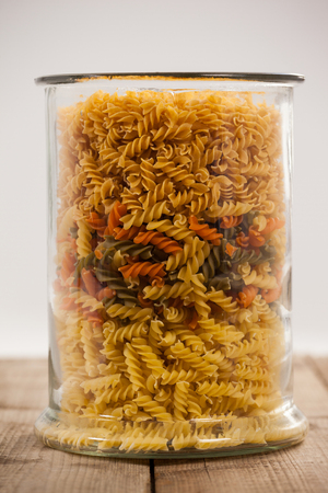 tight filled: Girandole pasta in a glass container on wooden table