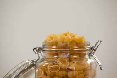 Conchiglie pasta in a jar on white background Stock Photo