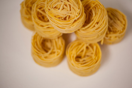 Tagliatelle pasta arranged in a row on white background