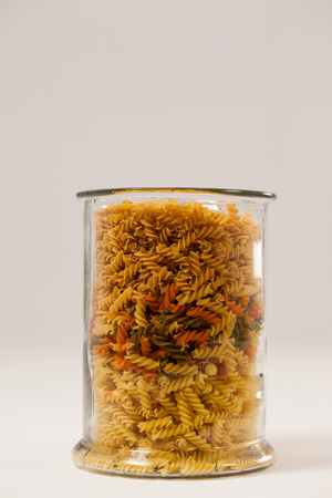 Girandole pasta in a glass container against white background