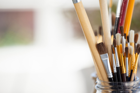 Set of paint brushes in a jar on wooden table Stock Photo