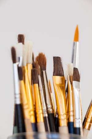 Varieties of paint brushes in glass jar against white background