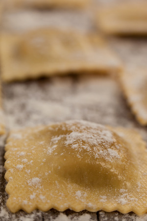 Close-up of ravioli pasta dusted with floor on wooden background