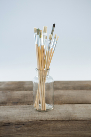 Various paintbrush in glass jar against white background