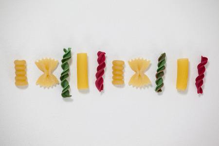 Varieties of pasta arranged on white background