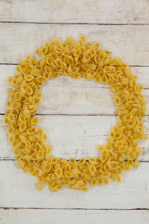 Fettuccine pasta forming a circle on wooden table Stock Photo