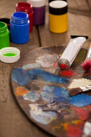 Palette with multiple colors, watercolor and paint brushes on wooden table Stock Photo