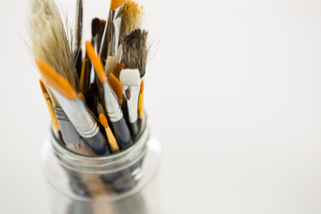 Close-up of various paintbrush in a jar on white background