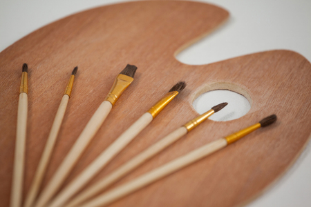 Wooden palette and paint brushes on wooden table