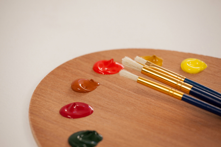 Palette with multiple colors and paint brushes on wooden table Stock Photo