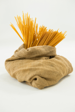 carbohydrates: Sack full of spaghetti pasta on white background