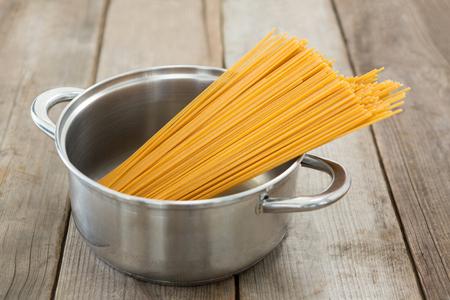 Spaghetti pasta in utensil on wooden surface