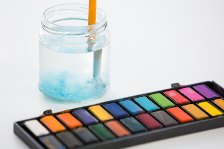dissolve: Close-up of colorful palette and jar on white background